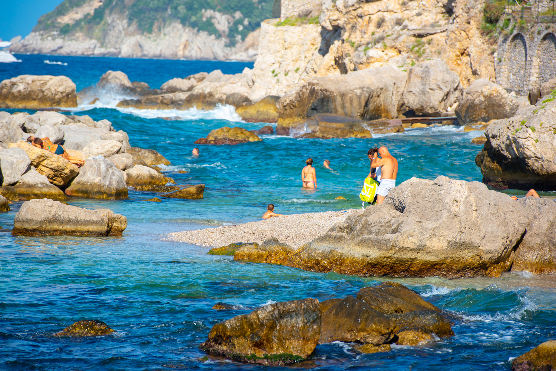 Beachgoers enjoying a summer's day at the Bagni di Tiberio in Capri, Italy.